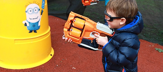 Photo of young boy aiming Nerf Gun at Minion