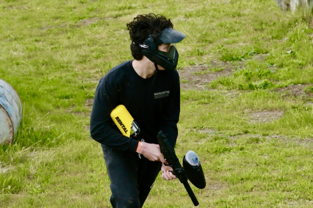 Photo of paintball player wearing all black standing in grass