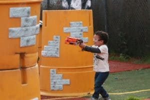 Photo of boy playing Nerf Wars near orange barriers
