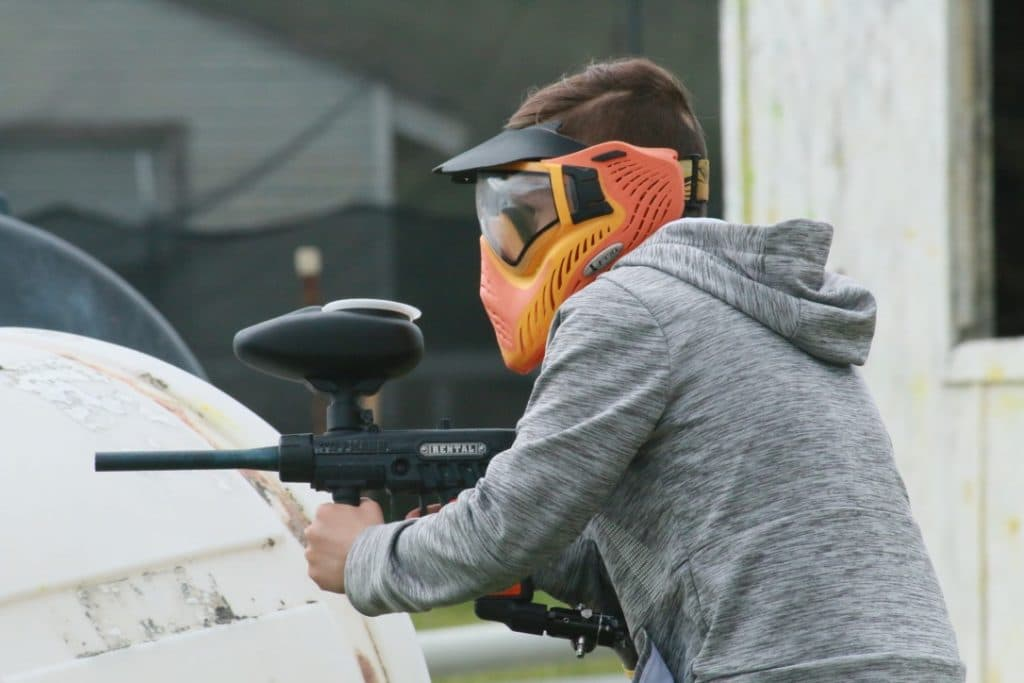 Photo of male playing paintball in grey sweatshirt