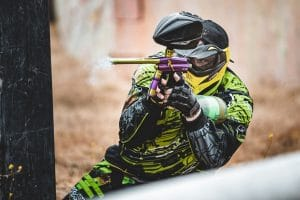 Photo of paintball player in yellow outfit firing marker