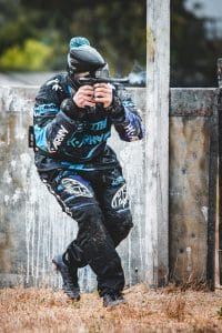 Photo of paintball player on blue team firing marker