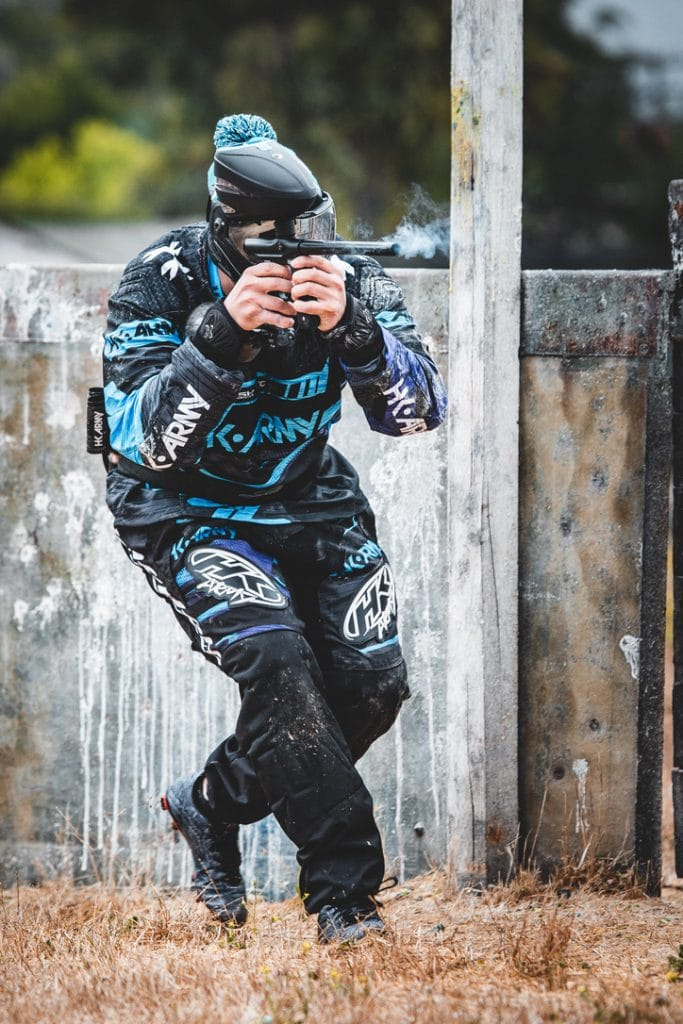 Photo of paintball player running and shooting