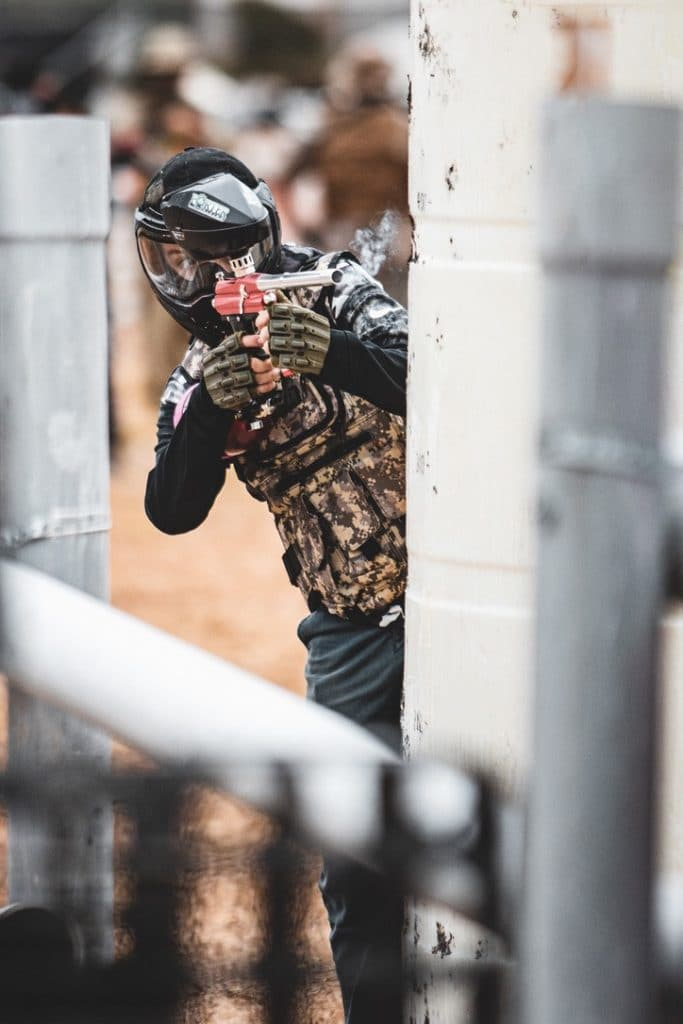 Photo of paintball player firing marker behind barrier