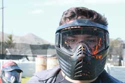 Photo of paintball player with paint on facemask